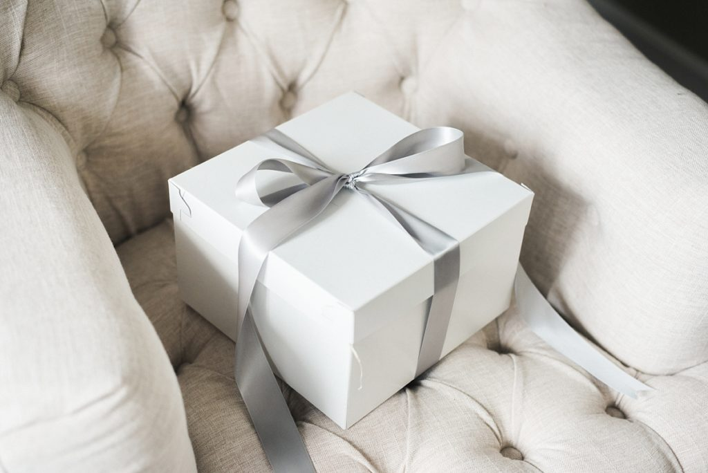 White gift box wrapped in gray ribbon